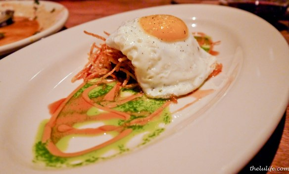 Wood oven roasted pig face topped with a sunny side egg with tamarind, cilantro, red wine maple and potato stix